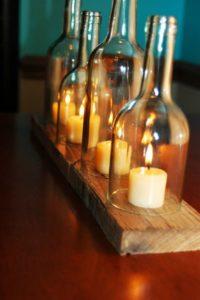 bouteilles-coupée-en-deux-avec-bougies-sur-plaque-de bois